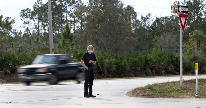 A man makes his way from the First Step Shelter across busy U.S.  Highway 92 to a bus stop on Red John Drive in Daytona Beach on Monday, Jan. 25, 2021. Early Monday morning, a resident of the shelter was killed crossing the highway trying to get to the bus stop.