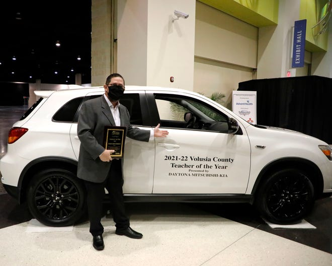 Volusia County Teacher of the Year Frank Garaitonandia poses in front of his new car at Ocean Center on Jan. 24, 2021.