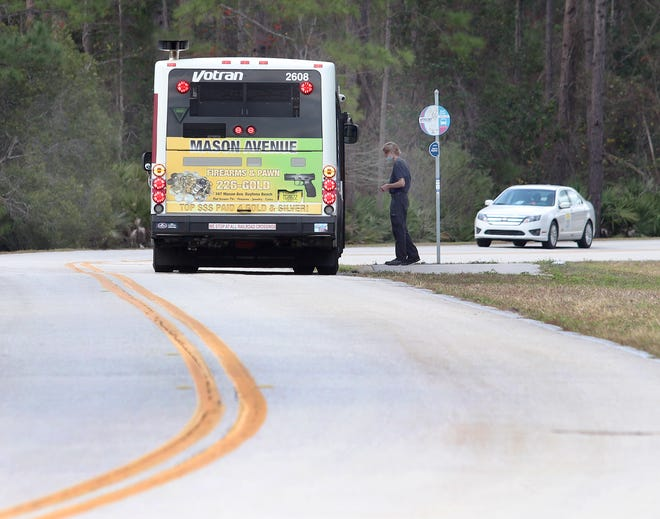 A First Step Shelter resident boards a Votran bus at on Red John Drive near U.S. 92.