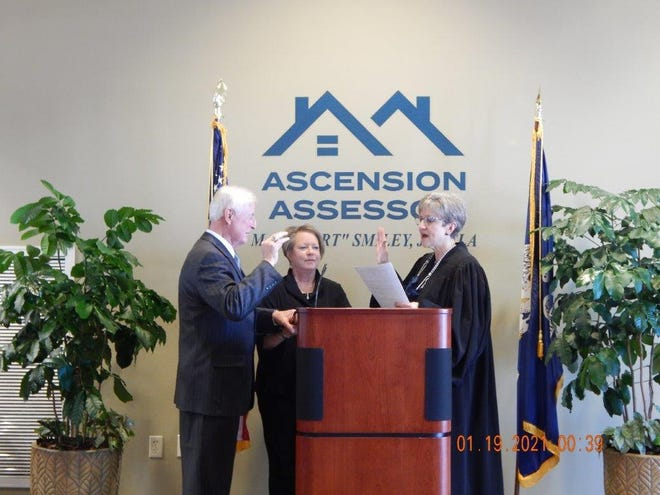 "Assessor M.J. ""Mert"" Smiley takes the oath of office with Judge Marilyn Lambert as Smiley's wife, Ina Smiley, looks on."