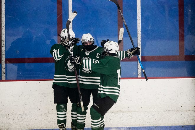 Abington's Michael Pineau, Senior Captain John Polito and Senior Captain David McArthur celebrate after McArthur scores for the Green Wave with an asset by Polito to put the score at 3-1 over Cohasset on Sunday, Jan. 24, 2021 at the Rockland Ice Rink.