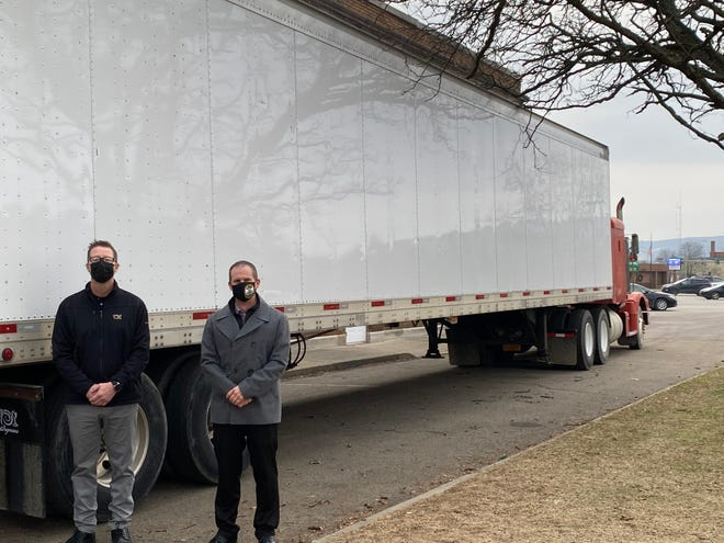 Hornell Wegmans store manager Brett Ahrens, left, with City of Hornell Mayor John Buckley and the trailer donated by Wegmans to store the city's Christmas tree.