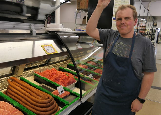 Dale Franz, the head butcher at Dale's Grocery in Hillsboro, holds up the front of the meat case.
