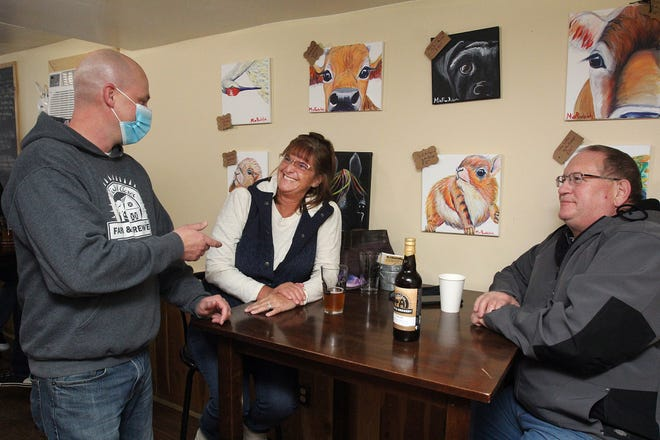 Nate Peterson, left, converses with Sue Baumgartner, center, and Curt Baumgartner of Pearl City on Saturday, Jan. 23, 2021, at Wishful Acres Farm & Brewery in rural Lena. Bars and restaurants have been able to return to indoor dining as the region's coronavirus metrics have improved.