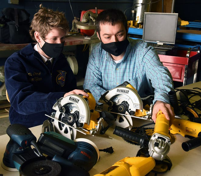 South Lenoir High School teacher Joshua Singleton and Brody Lynch, a freshman in the agriculture education curriculum, sort tools in ag mechanics class. A $3,000 grant awarded Singleton by AgCarolina Farm Credit will help refurbish the workshop where Brody and fellow students get hands-on practice in skills like welding and metalworking. [CONTRIBUTED PHOTO]
