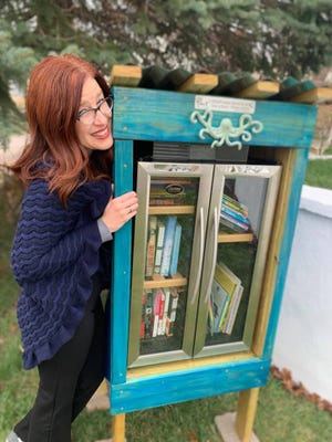 Brenda O'Neill stands next to her blue-hued Little Free Library that stands in front of her Penn Street home.
