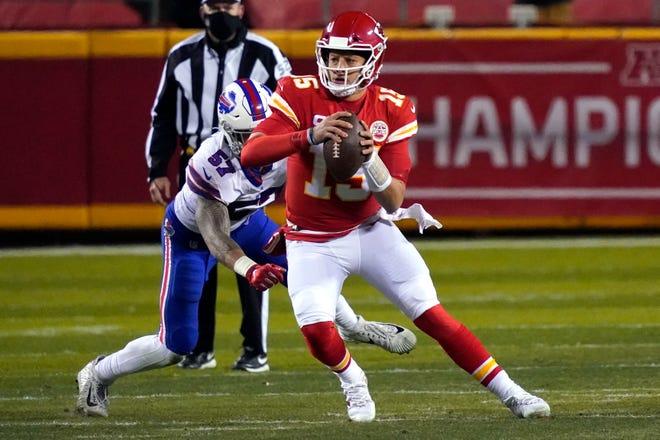 Kansas City Chiefs quarterback Patrick Mahomes (15) scrambles up field ahead of Buffalo Bills defensive end AJ Epenesa (57) during the first half of the AFC championship NFL football game, Sunday, Jan. 24, 2021, in Kansas City, Mo.