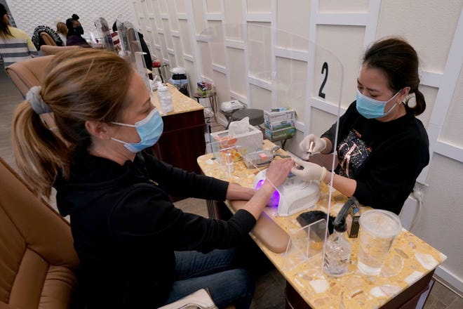 Sara Nguyen, right, sits behind a plexiglass shield as she gives a manicure to Christine Frazer Monday at KB Nails in Sacramento. Gov. Gavin Newsom lifted stay-at-home orders across the state Monday allowing restaurants and churches to resume outdoor operations and hair and nail salons to reopen in many areas. The state lifted restrictions in the Sacramento area two weeks ago.