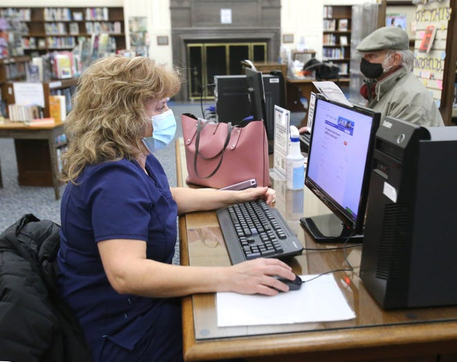 Kathy Cottrill works on a computer at the Massillon Public Library on Monday. In the background is Jim Walker. After the pandemic shut down the library in March, patrons are returning.