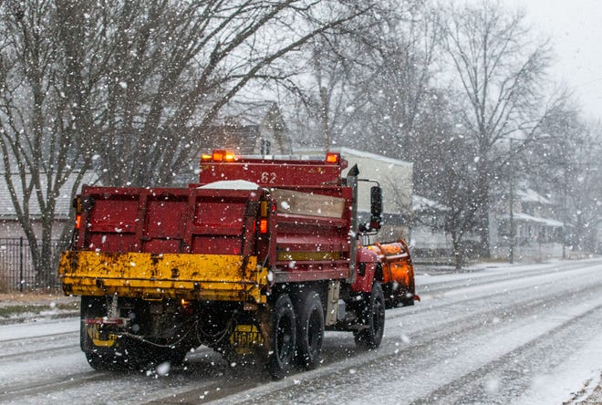 A Public Works truck spreads salt along Lawrence Avenue as heavy snow comes down during the morning commute as a Winter Weather Advisory is in place for the area on Monday, January 25, 2021, in Springfield, Ill. According to the National Weather Service in Lincoln the snow will transition into freezing rain through the morning with temperatures rising above freezing by noon. [Justin L. Fowler/The State Journal-Register]