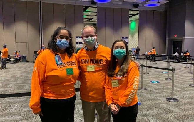 Congressman Greg Murphy, center, stands with two Vidant Medical Center workers at Greenville's mass vaccination clinic on Monday.  Both Murphy and Craven County Health Director Scott Harrelson believe the state could do better in getting vaccines out. [Contributed photo]