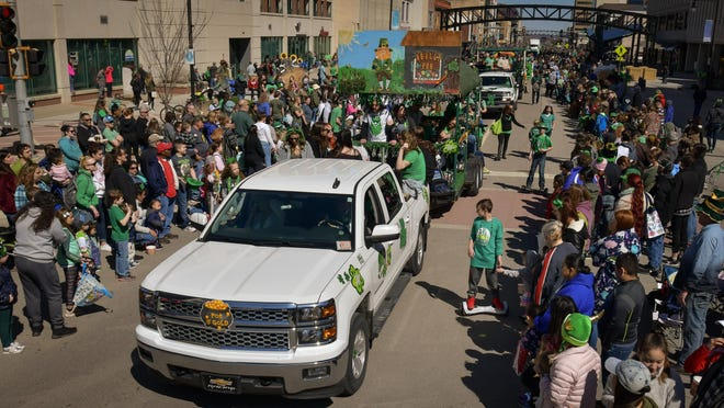 A large crowd of people lines the streets as St. Patrick's Day floats move along S. Kansas Avenue in 2019.