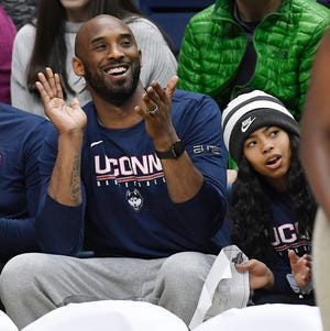 In this March 2, 2019 photo, Kobe Bryant and his daughter Gianna watch the first half of an NCAA college basketball game between Connecticut and Houston in Storrs, Conn. Bryant, the 18-time NBA All-Star who won five championships and became one of the greatest basketball players of his generation during a 20-year career with the Los Angeles Lakers, died in a helicopter crash on Jan. 26, 2020. Gianna also died in the crash.