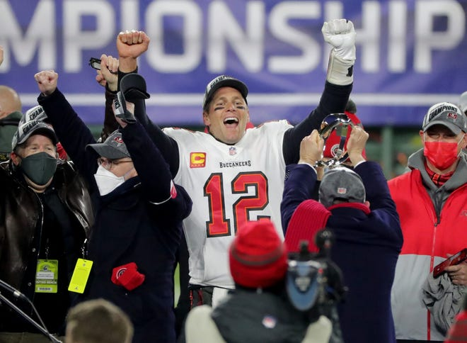 Buccaneers quarterback Tom Brady exalts during the presentation of the George Halas Trophy after Tampa Bay earned a berth in the Super Bowl.