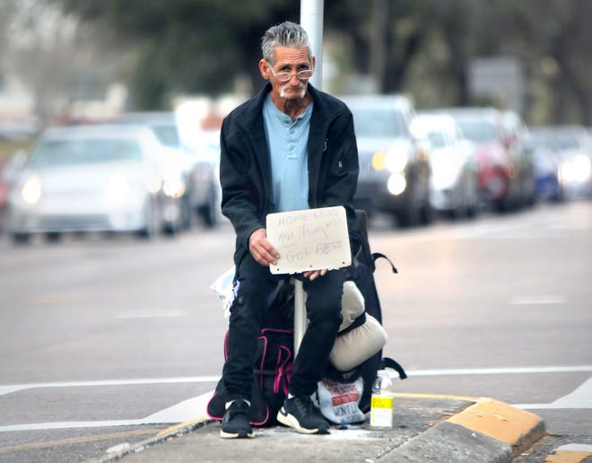 A man holds a sign that asks passing drivers for money at Southwest 13th Street near Archer Road in Gainesville last week. A proposed Gainesville ordinance would fine thosewho stand or sit in some traffic medians. [Brad McClenny/The Gainesville Sun]