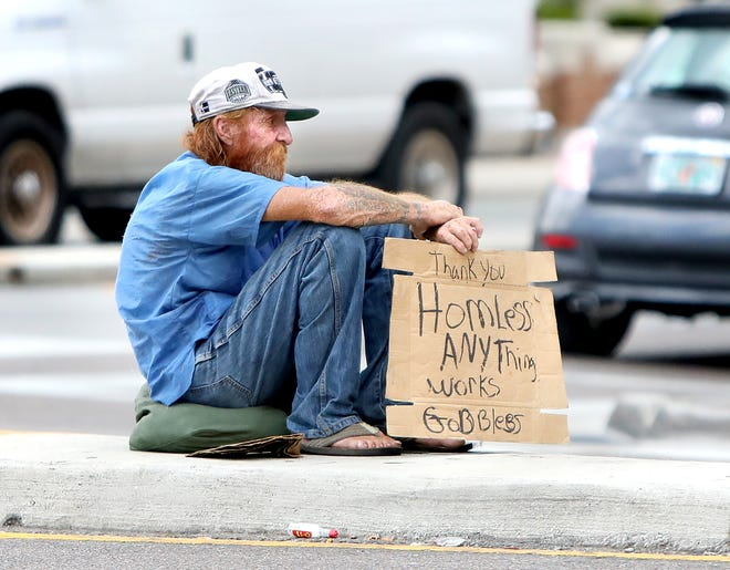 A man asking for help from passing drivers sits in the median of Northwest 13th Street in Gainesville in late June.