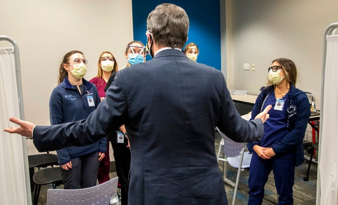 North Carolina Gov. Roy Cooper thanks physician assistant students while touring a large-scale vaccination site at UNC's Friday Center in Chapel Hill Tuesday, Jan. 19 2021. UNC Hospitals hope to administer 2500 first COVID-19 vaccine doses at the Friday Center by the end of this week. (Travis Long/The News & Observer via AP)