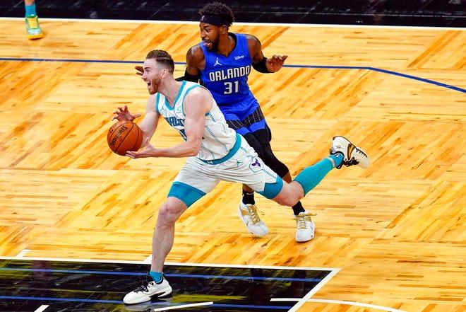 Charlotte Hornets forward Gordon Hayward, left, drives past Orlando Magic guard Terrence Ross (31) during the second half of an NBA basketball game, Sunday, Jan. 24, 2021, in Orlando, Fla. (AP Photo/John Raoux)