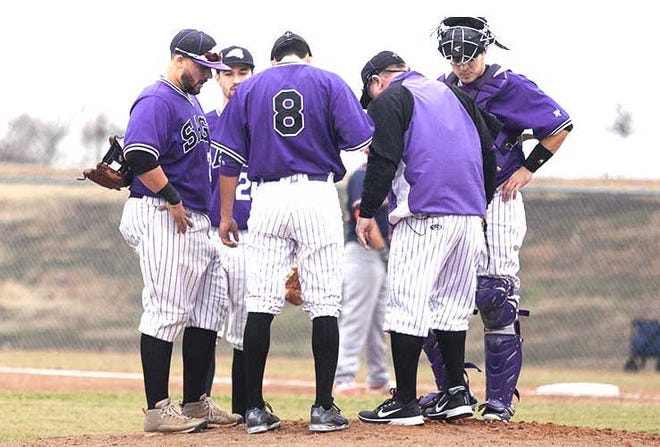 Southwestern Assemblies of God players huddle at the pitcher's mound during a 2020 home game.