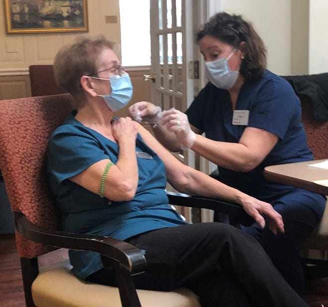 New Horizons assisted living aide Mary Traer receives a vaccine from a CVS team member.