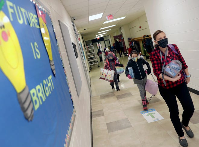First-grade teacher Erin Mohr leads her students to the their Highlands Elementary classroom as students in January, the Appleton Area School District returned to in-person schooling. The district is aiming to get all of its staffers the first round of the vaccine by the end of this month.