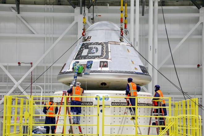 Technicians assist the Starliner crew module being placed on top of the service module in the Commercial Crew and Cargo Processing Facility at Kennedy Space Center.