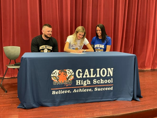 Galion's Samantha Comer signs her letter of intent to continue her volleyball career at Notre Dame College.  L to R: stepfather Tim McDaniel, Samantha Comer, mother Denise McDaniel