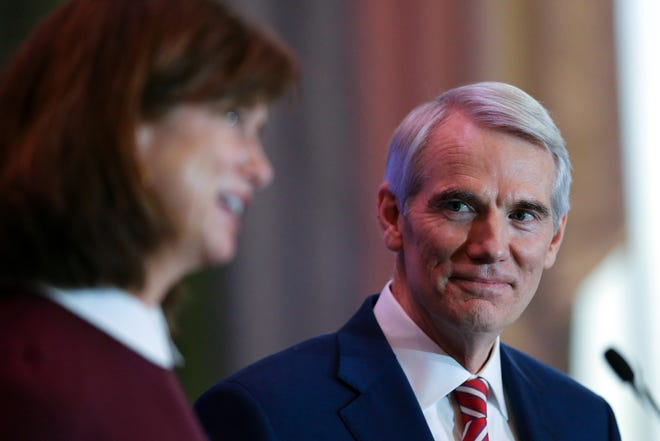 U.S. Sen. Rob Portman listens as his wife Jane answers a question after he announced he will not be seeking re-election when his term is up in 2022, Monday, Jan. 25, 2021, at the Hilton Hotel in Cincinnati.