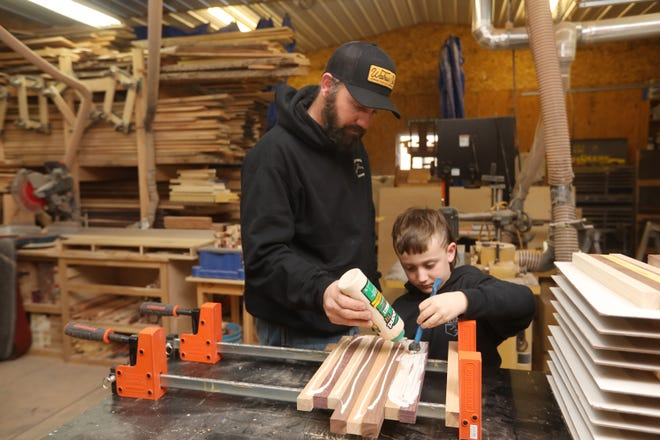 Justin Lapp and his son Jacoby work on cutting board at Lapp's Broken Arrow Woodworking workshop near Warsaw. Lapp is best known for his cutting boads, but also does a variety of other woodworking.