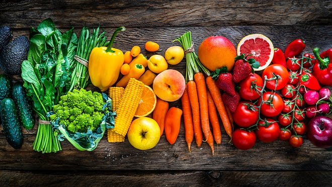 Large assortment of healthy fresh rainbow colored organic fruits and vegetables arranged side by side on rustic wooden table. The composition includes carrots, onion, tomatoes, avocado, corn, green bean, cucumber, broccoli, spinach, apples, strawberries, mango, grape fruit, peach, oranges, bell pepper, radish among others.