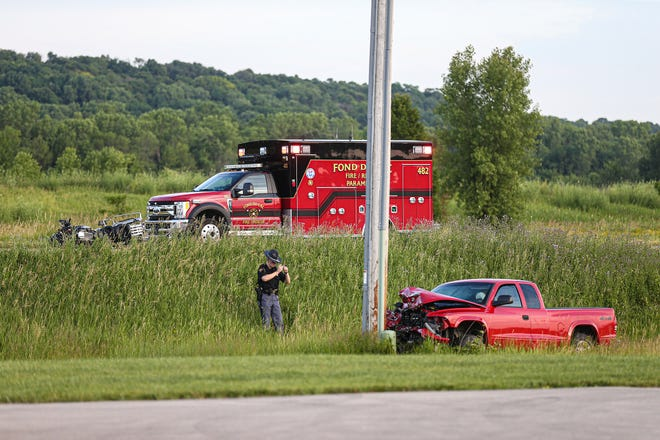 A Wisconsin State Patrol officer takes photos of a crash scene involving a red pick-up truck and a motorcycle  July 3  on Winnebago Drive near State Highway 151 northeast of Fond du Lac.