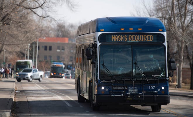 """An electronic sign on the front of a Transfort bus reads """"masks required"""" as it drives through the Colorado State University campus on Monday, Jan. 25, 2021."""