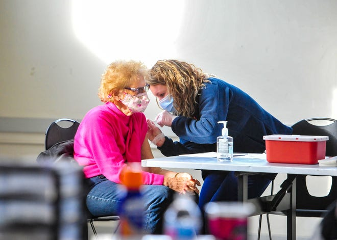D. Perry receives her COVID-19 vaccination from Great Falls Clinic nurse Mary Allen during a vaccination clinic in the Family Living Center building at Montana ExpoPark.