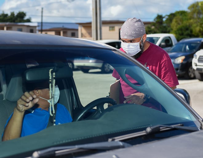 Driver's license examiner Van C. Morada assists a customer in the Guam Department of Revenue and Taxation parking lot in this Jan. 25 file photo.