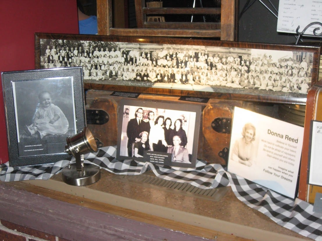 A window display dedicated to Donna Reed currently on display at the Donna Reed Heritage Museum in Denison, Iowa -- the town of her birth -- to celebrate the actress's centennial. According to museum volunteers, the display will likely remain up until May 2021.