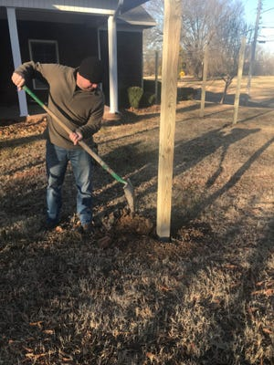 Craig Barton, a member of Leadership Jackson fills in a hole around a post in the fence.