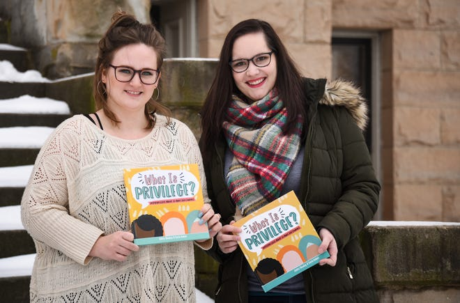 """""""What is Privilege?"""" co-authors Kayla DeWalt, left, East Lansing, and Ashley Gooding of Hastings pose for a portrait, Monday, Jan. 25, 2021, at the historic Eaton County Courthouse in Charlotte.  The two met online.  Both illustrated and wrote, and published the book, which was released on Jan 20."""