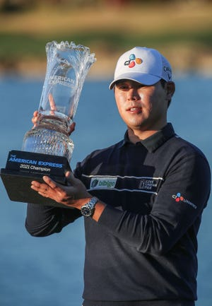 Si Woo Kim holds the trophy after winning the American Express at PGA West in La Quinta, January 24, 2021.