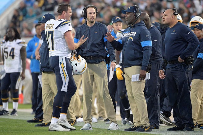 Los Angeles Chargers quarterback Philip Rivers (17) talks with head coach Anthony Lynn and offensive coordinator Shane Steichen, center, during a timeout in the first half of an NFL football game against the Jacksonville Jaguars Sunday, Dec. 8, 2019, in Jacksonville, Fla. (AP Photo/Phelan M. Ebenhack)