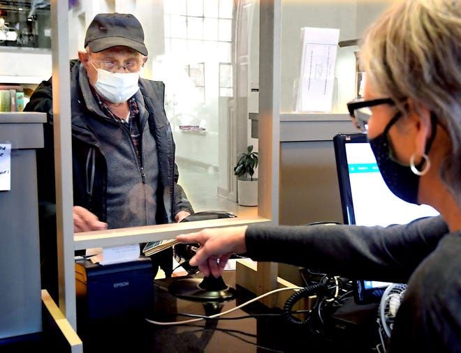 Lynn Henry of York Township checks out books with library assistant Ileana Campagne at Martin Library in York City Monday, Jan. 25, 2021. York County Libraries reopened for in-library browsing Monday. Kreutz Creek Library in Hellam will continue with lobby pickup only and Village Library in Jacobus will offer browsing services by appointment. Outside the children's library, Martin Library offers seniors-only hours on Mondays from 10 a.m. to 1 p.m. To check individual library hours, go to open.yorklibraries.org. Bill Kalina photo