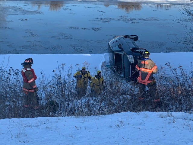 Merrill firefighters rescue a man whose van ended up on its side on the ice of the Wisconsin River Monday morning.