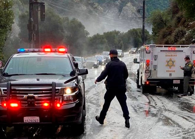 In this Saturday, Jan. 23, 2021, photo provided by the California Highway Patrol-West Valley, authorities work the scene of an accident after a hail storm on Malibu Canyon Road in Malibu, Calif.