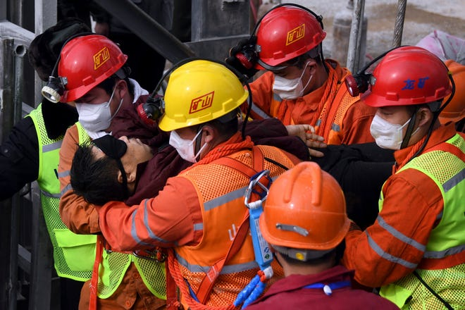 Rescuers carry a miner to an ambulance in Qixia City in east China's Shandong Province, one of 11 miners trapped for two weeks who were brought safely to the surface on Sunday.