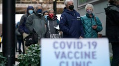 People wait in line to receive the first of two doses of the Pfizer COVID-19 vaccine on Sunday at a one-day vaccination clinic set up in an Amazon.com facility in Seattle and operated by Virginia Mason Franciscan Health.