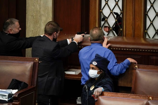 Police with guns drawn watch as pro-Trump rioters try to break into the House Chamber at the U.S. Capitol on Jan. 6, in Washington.