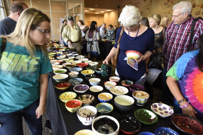 Attendees to the 2018 Empty Bowl Project fundraiser for the Bastrop County Emergency Food Pantry select a hand-painted bowl from a colorful assortment before sampling soups by restaurants in the Bastrop Convention Center lobby. This year, the annual fundraiser will be held online.