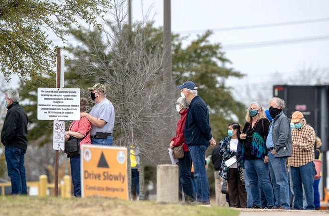Hundreds of people who made an appointment to be vaccinated from COVID-19 stand in a line that wraps around the building at the Delco Activity Center in Northeast Austin in January.