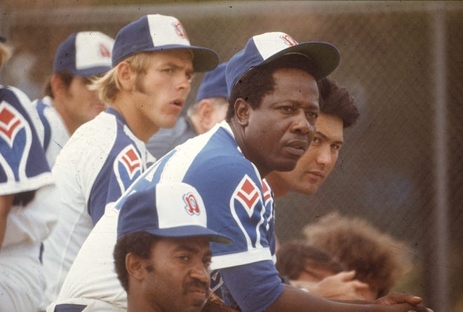 Hank Aaron watches a game from the dugout.