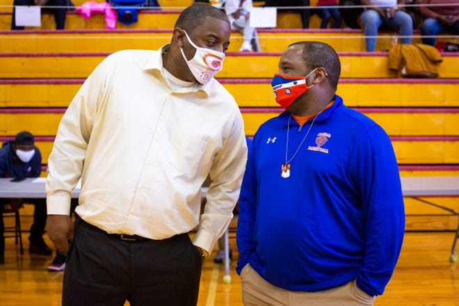 Clarke Central head coach Stefan Smith (left) and Cedar Shoals head coach Dreco Thomas talk before a boys high school basketball game at Clarke Central High School on Saturday. A tight game throughout, Clarke Central sealed the deal in double overtime to win 51-44. (Casey Sykes for The Athens Banner-Herald)