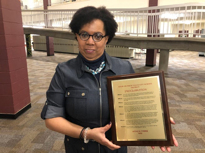Laura Farris-Daugherty holds a plaque that honors her mother, Leona Farris. The Stow-Munroe Falls City School District gave one plaque to Farris, and its twin will hang at the entrance of Stow-Munroe Falls High School.